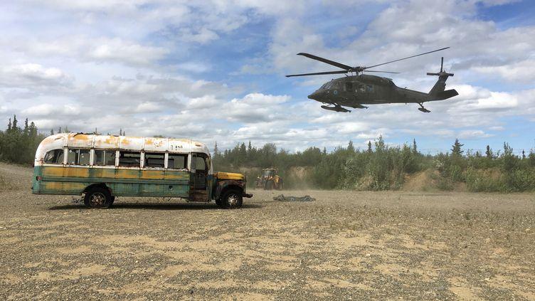 """Un hélicoptère de la garde nationale s'apprête à transporter une épave de bus rendue célèbre par le film """"Into the Wild"""", le 18 juin 2020, en Alaska (Etats-Unis). (ALASKA DEPARTMENT OF NATURAL RESOURCES / REUTERS)"""