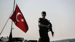 Un policier turc d'une unité anti-émeute se tient sur un tank après latentative de putsch, le 16 juillet 2016. (OZAN KOSE / AFP)