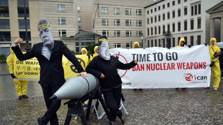 Des militants de l'Ican portant des masques deDonald Trump et Kim Jong-un manifestent pour l'abolition des armes nucléaires, le 13 septembre 2017, devant l'ambassade des Etats-Unis à Berlin (Allemagne). (BRITTA PEDERSEN / DPA / AFP)
