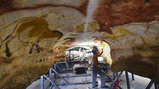 Un artisan travaille sur la réplique de la grotte de Lascaux, dont l'ouverture est prévue en décembre 2016. (MEHDI FEDOUACH / AFP)