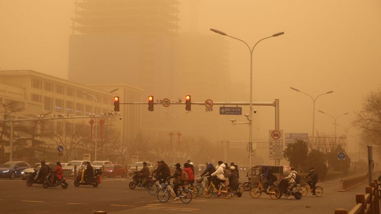 Des usagers de la route dans la tempête de sable et la pollution à Pékin, le 15 mars 2021. (KOKI KATAOKA / YOMIURI / AFP)