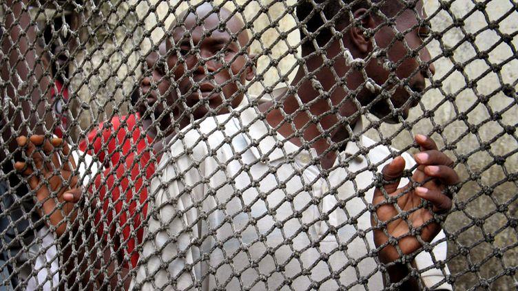 Des détenus derrière une grille de la prison centrale de Douala, au Cameroun. La surpopulation carcérale y est particulièrement éprouvante. (GABRIELA MATTHEWS / X02030)