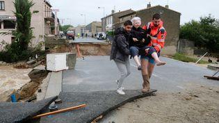 Une femme est évacuée, le 15 octobre 2018, àVillegailhenc (Aude), après des inondations. (ERIC CABANIS / AFP)