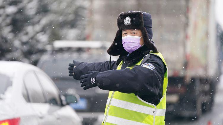 Un policier fait la circulation à Harbin (nord-est), sur un check-point routier de prévention de l'épidémie de coronavirus. (WANG JIANWEI / XINHUA / AFP)