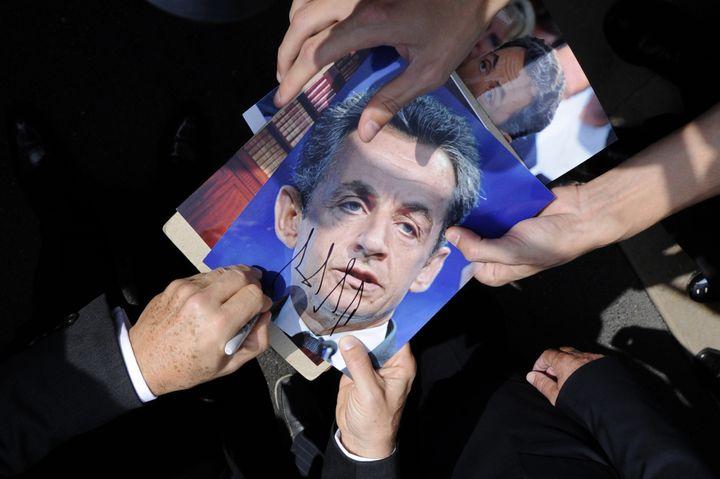 L'ancien président, Nicolas Sarkozy, signe un autographe, le 27 septembre 2013 à Nice. (OLIVIER ANRIGO / REUTERS)