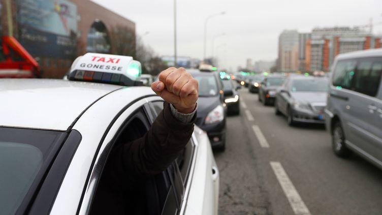 Des chauffeurs de taxi manifestent le 10 janvier 2013 sur le périphérique parisien. (KENZO TRIBOUILLARD / AFP)