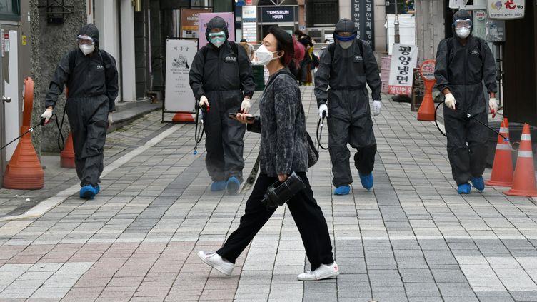 Une femme passe devant des responsables sanitaires sud-coréens pulvérisant des désinfectants dans un quartier commercial d'Incheon dans le nord du pays, le 17 septembre 2020 (photo d'illustration). (JUNG YEON-JE / AFP)