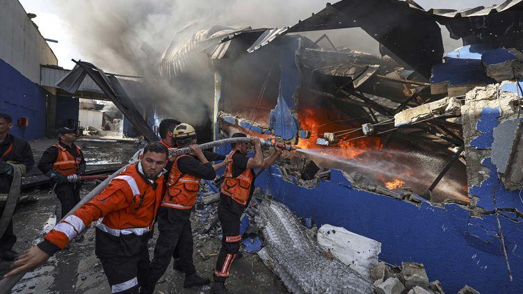 Des pompiers à Gaza tentent d'éteindre un incendie après une frappe aérienne, le 17 mai 2021. (MAHMUD HAMS / AFP)