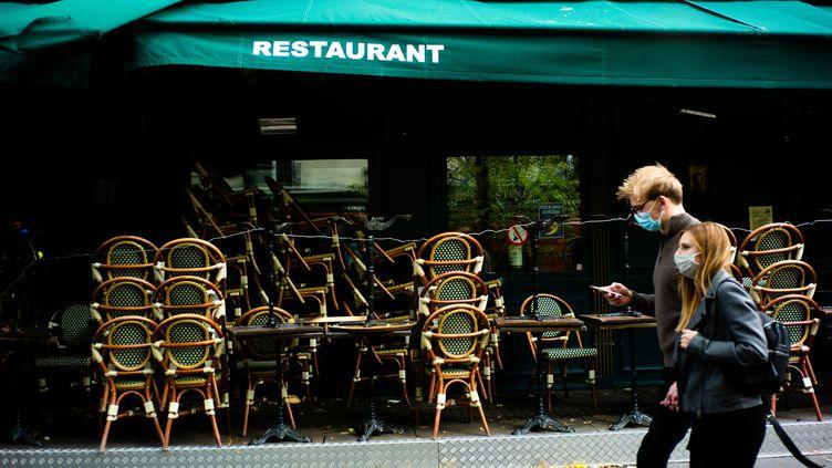 Deux personnes passant devant un bar-restaurant fermé à Paris, le 21 octobre 2020. (EDOUARD RICHARD / HANS LUCAS / VIA AFP)