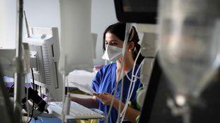 Une soignante au chevet d'un patient hospitalisé en réanimation, le 8 mars 2021 à Boulogne-Billancourt (Hauts-de-Seine). (ALAIN JOCARD / AFP)