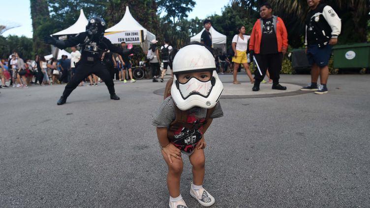 """Un enfant porte un casque de Stormtrooper, personnage de Star Wars, lors du """"Star Wars day"""", le 4 mai 2017 à Singapour. (ROSLAN RAHMAN / AFP)"""