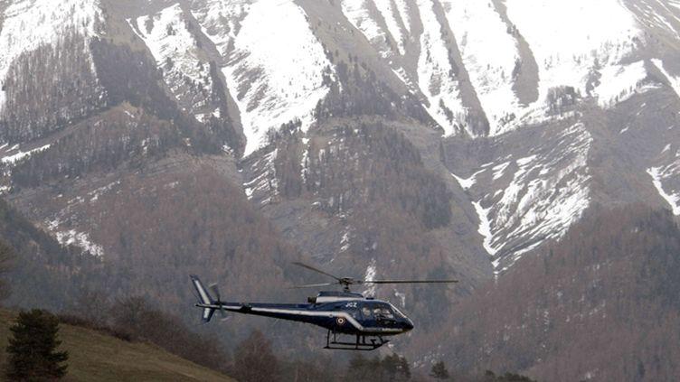 (Les hélicoptères survolent depuis plusieurs heures les lieux du crash de l'appareil de Germanwings © AP/SIPA/Claude Paris)