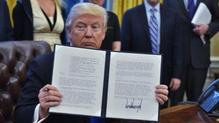 Le président américain, Donald Trump, brandissant le décret qu'il vient de signer dans le bureau ovale, le 28 janvier 2017, en faveur de l'éradication de Daech en Irak et en Syrie. (MANDEL NGAN / AFP)