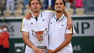 La paire française, composée de Pierre-Hugues Herbert et Nicolas Mahut, a décroché un deuxième titre à Roland-Garros, samedi 12 juin. (ANNE-CHRISTINE POUJOULAT / AFP)