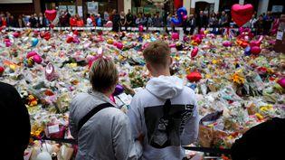 Des passants se recueillent, le 29 mai 2017 à Manchester (Royaume-Uni), devant le mémorial improvisé aux victimes de l'attentat. (PHIL NOBLE / REUTERS)