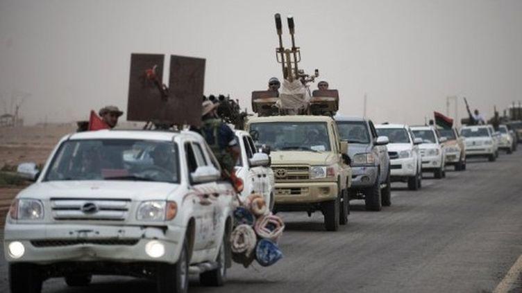 Les rebelles libyens sur la route entre Ajdabiya et Brega, ville pétrolière située sur la ligne de front (14/07/2011). (GIANLUIGI GUERCIA / AFP)