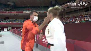 Capture d'écran de la vidéo montrant l'entraîneur de la judokate allemande Martyna Trajdos en train de lui mettre des petites claques avant son entrée sur le tatami, mardi 27 juillet 2021. (FRANCEINFO SPORT)