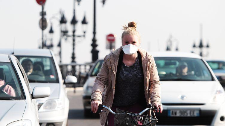 Une jeune femme portant un masque lors d'un pic de pollution à Bordeaux, le 14 mars 2014 (photo d'illustration). (BONNAUD GUILLAUME / MAXPPP)