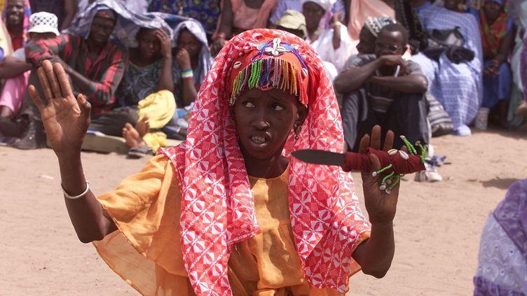 Une jeune femme mime le rituel de l'excision, un couteau à la main, lors d'une réunion contre cette pratique, à Kolda (Sénégal) en 2002. (SEYLLOU DIALLO / AFP)