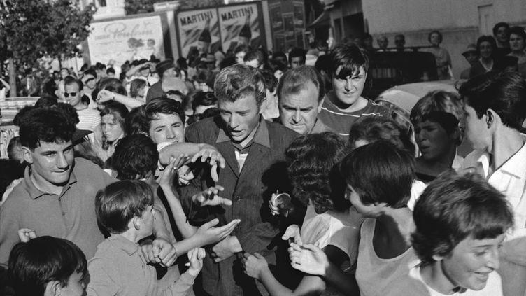 Johnny Hallyday entourés de fans à Cannes, le 28 août 1962. (UPI / AFP)