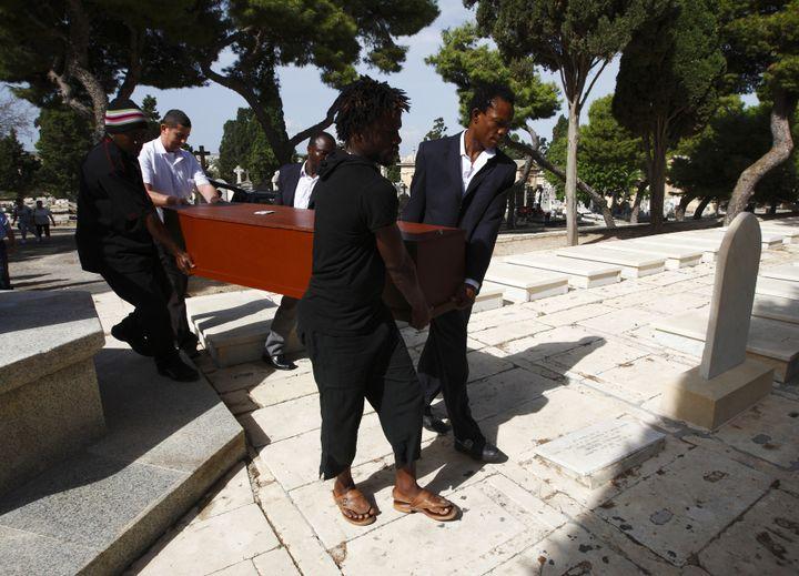 Des migrants d'origine africaine portent le cercueil d'un Nigérian mort lors du naufrage d'un bateau en Méditerranée, au cimetière Addolorata de La Valette (Malte), le 16 octobre 2012. (DARRIN ZAMMIT LUPI / REUTERS)