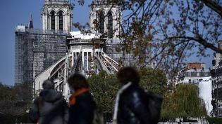 Des passants regardent la cathédrale Notre-Dame en chantier, à Paris le 14 avril 2021. (ANNE-CHRISTINE POUJOULAT / AFP)