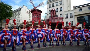 Les danseuses du Moulin rouge sur le Boulevard de Clichy pour annoncer la réouverture du cabaret en septembre, le 17 mai 2021 (MARTIN BUREAU / AFP)