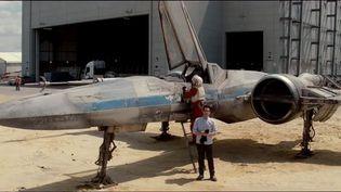 """Le réalisateur américain J.J. Abrams, devant le X-Wing, conduit dans le 4e volet de la saga """"Star Wars"""" par Luke Skywalker. (WWW.OMAZE.COM / STARWARS / LUCASFILM LTD.)"""