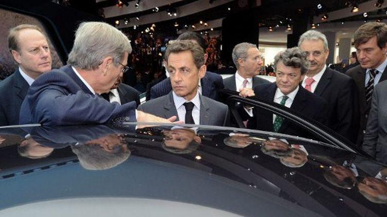 Nicolas Sarkozy écoutant le patron de PSA Philippe Varin au salon de l'Automobile (1er octobre 2010) (AFP/Lionel Bonaventure)