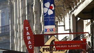 """La """"carotte"""" d'un bureau de tabac à côté de l'enseigne de la Française des jeux. (ALEX BAILLAUD / MAXPPP)"""