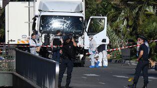 Des policiers inspectent le camion utilisé lors de l'attaque à Nice (Alpes-Maritimes), le 15 juillet 2016. (ANNE-CHRISTINE POUJOULAT / AFP)
