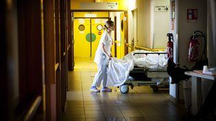 Une infirmière travaillant de nuit dans un hôpital d'Aulnay-sous-Bois (Seine-Saint-Denis) pousse un patient, le 14 novembre 2012. (AMELIE BENOIST / AFP)