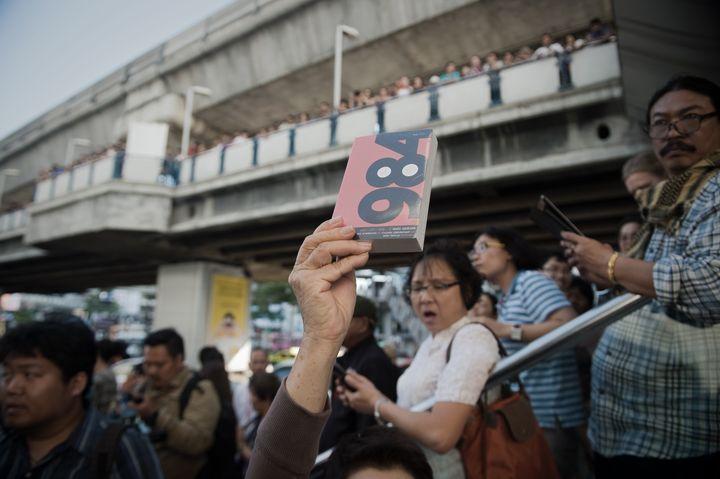 Un manifestant brandit1984, de George Orwell, à Bangkok (NICOLAS ASFOURI / AFP)