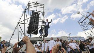 Perché sur un échafaudage, Juan Guaido salue ses supporters, le 4 mars 2019, à Caracas (Venezuela). (FERNANDO LLANO/AP/SIPA / AP)