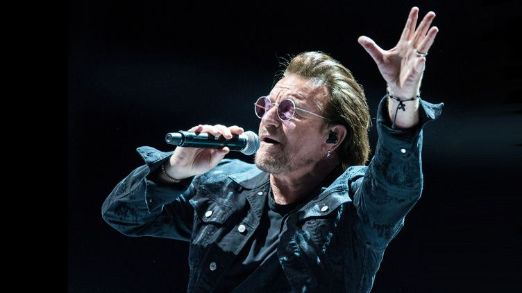 """Bono, le chanteur du groupe de rock irlandais U2, lors d'un concert le 3 octobre 2018 à Hambourg (Allemagne), dans le cadre de la tournée """"The eXPERIENCE + INNOCENCE"""". (DANIEL BOCKWOLDT / DPA / AFP)"""