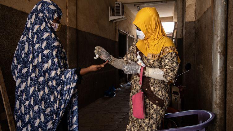 """Mosquée de Ouagadougou - Burkina Faso A l'entrée du lieu de prière réservé aux femmes, le """"pagb misri"""", l'une d'entre elles distribue du gel hydroalcoolique. La Fédération burkinabè des associations islamiques a annoncé la suspension des prières entre le 21 mars et le 4 avril. Alors que le pays connaît une progression du nombre de cas, le milieu hospitaliers'est aussi réjoui de quelques guérisons.  (OLYMPIA DE MAISMONT / AFP)"""