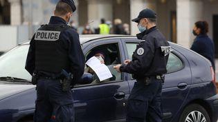 Deux policiers effectuent un contrôle du confinement, le 27 février, à Nice (Alpes-Maritimes). (VALERY HACHE / AFP)
