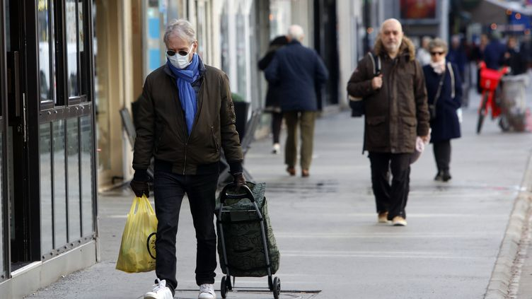 Un homme portant un masque de protection et des gants, faisant ses courses à Paris le 13 mars 2020. (MEHDI TAAMALLAH / NURPHOTO)