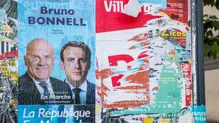 Une affiche d'un candidat aux législatives de la République en marche, collée à côté d'une affiche déchirée du Parti socialiste, à Villeurbanne, le 26 mai 2017. (KONRAD K. / SIPA)