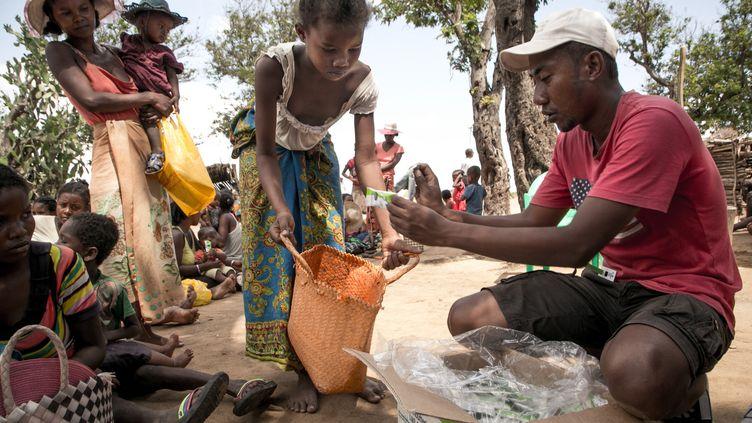 Un travailleur humanitaire de l'ONG Action contre la faim distribue des compléments alimentaires dans la commune d'Ifotaka, dans le sud de Madagascar, le 14 décembre 2018. (RIJASOLO / AFP)