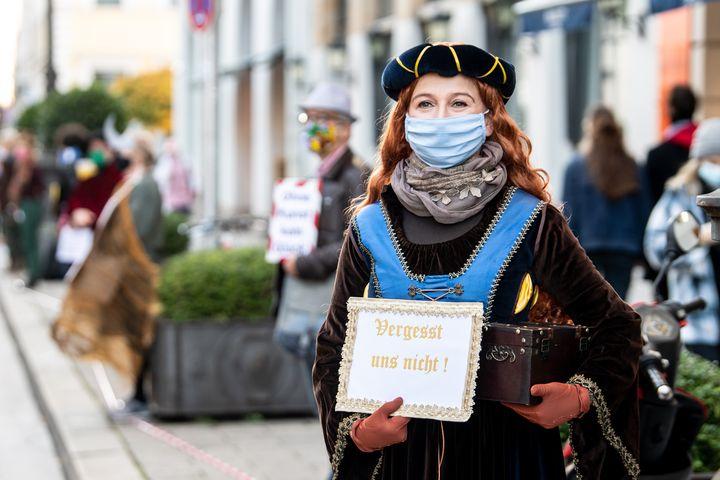 """Munich, 31 octobre 2020. Sabine, une actrice de l'Opéra d'État de Munich se prépare, avec sa pancarte """"Ne nous oubliez pas & nbsp;!"""" (ne nous oubliez pas) pour rejoindre la chaîne humaine reliant les employés et amis des différents théâtres de la ville en solidarité dans une perspective de recomposition partielle.  & nbsp;  (MATTHIAS BALK / DPA)"""
