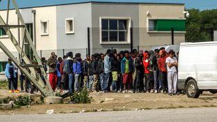 A Calais, des migrants font la queue devant un camion pour recevoir de la nourriture, le 4 août 2017. (PHILIPPE HUGUEN / AFP)