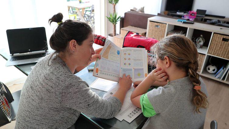 L'école se fait à la maison pendant le confinement et les devoirs des enfants sont la plupart du temps supervisés par les mères (photo d'illustration). (LAURENT THEILLET / MAXPPP)