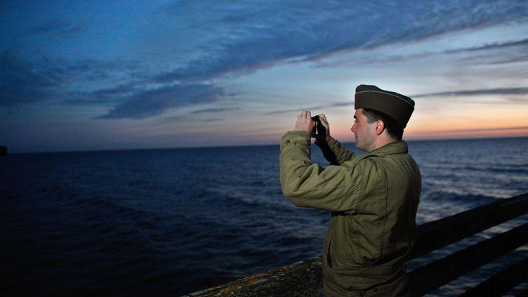Un amateur d'histoire en tenue militaire photographie Omaha Beach à l'aube,le 6 juin 2014. (THIBAULT CAMUS / AP / SIPA)