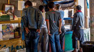"""Des migrants font la queue dans un restaurant de la """"jungle"""", à Calais (Pas-de-Calais), le 12 août 2016. (PHILIPPE HUGUEN / AFP)"""