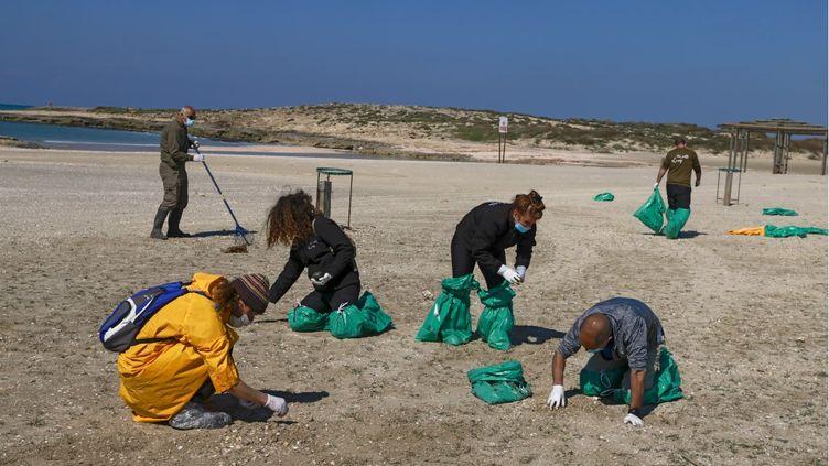Des personnes nettoient la plage vers Haïfa (Israël) souillée par des galettes de pétrole, le 21 février 2021.  (AFP)