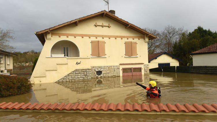 Un pompier inspecte un quartier inondé de Peyrehorade (Landes) le 14 décembre 2019. (GAIZKA IROZ / AFP)