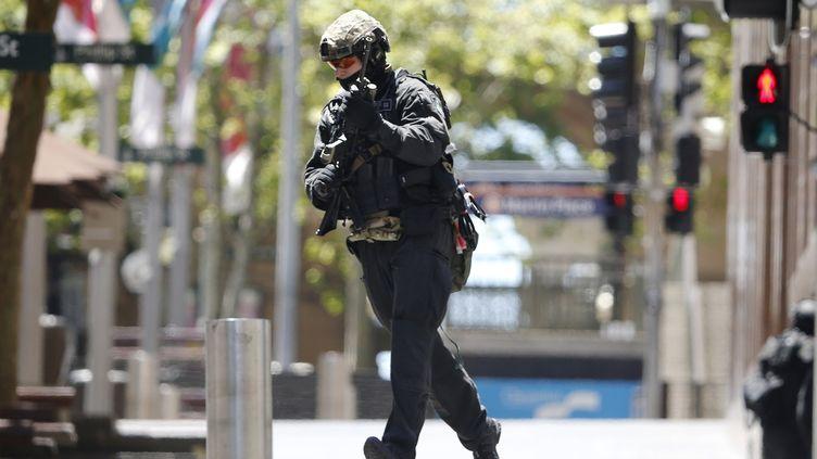 Un officier de police traverse Martin Place près du café Lindt où les otages sont détenus, dans le centre de Sydney (Australie), le 15 Décembre, 2014 (JASON REED / REUTERS )