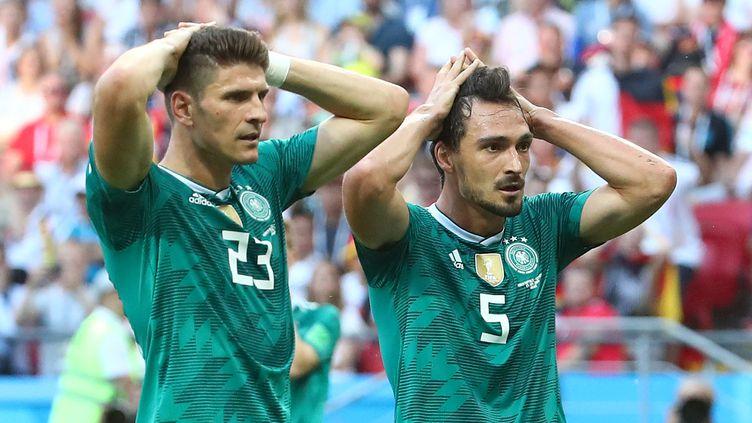Les Allemands Mario Gomez et Mats Hummels se tiennent la tête après un tir manqué, le 27 juin 2018, face à la Corée du Sud, à Kazan (Russie). (MICHAEL DALDER / REUTERS)