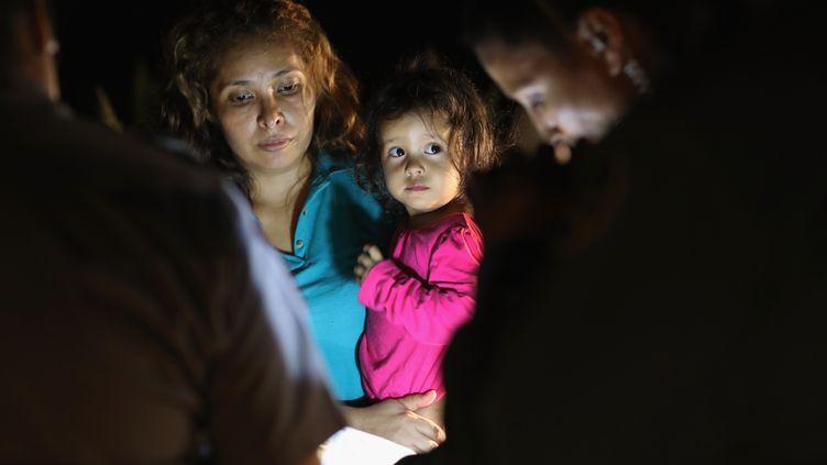 Une mère et sa fille de 2 ans, en provenance du Honduras, arrêtées près de la frontière entre le Mexique et les Etats-Unis, à McAllen, au Texas, le 12 juin 2018. (JOHN MOORE / GETTY IMAGES NORTH AMERICA / AFP)